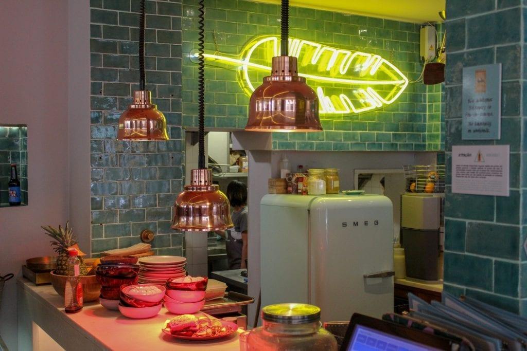 Imagem mostra o balcão e parte da cozinha de uma lanchonete, com luzes acesas, geladeira e outros utensílios de cozinha.