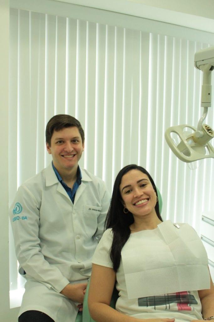 Dentista Vinícius, sentado ao lado de uma paciente em sua clínica odontológica